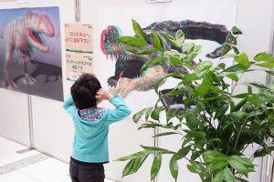 3D恐竜展ポスターを見るお子さん